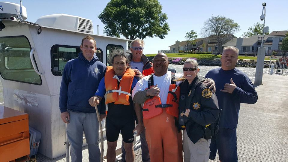 The rescued boater, second from left, with his rescuers from the U.S. Army Corps of Engineers and the Sheriff's Office Marine Services Unit.