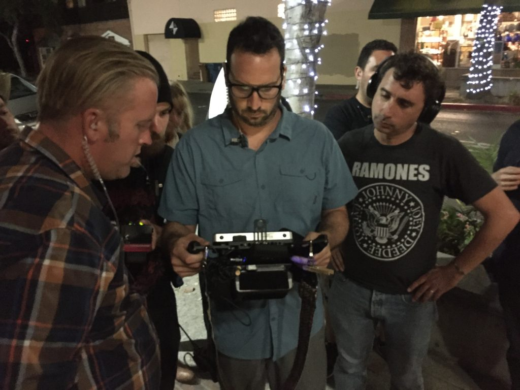 Director Anthony C. Ferrante (right, in Ramones shirt) watches the shooting on a monitor with some of his crew outside the El Campanil Theatre in downtown Antioch, Monday night, August 22, 2016.