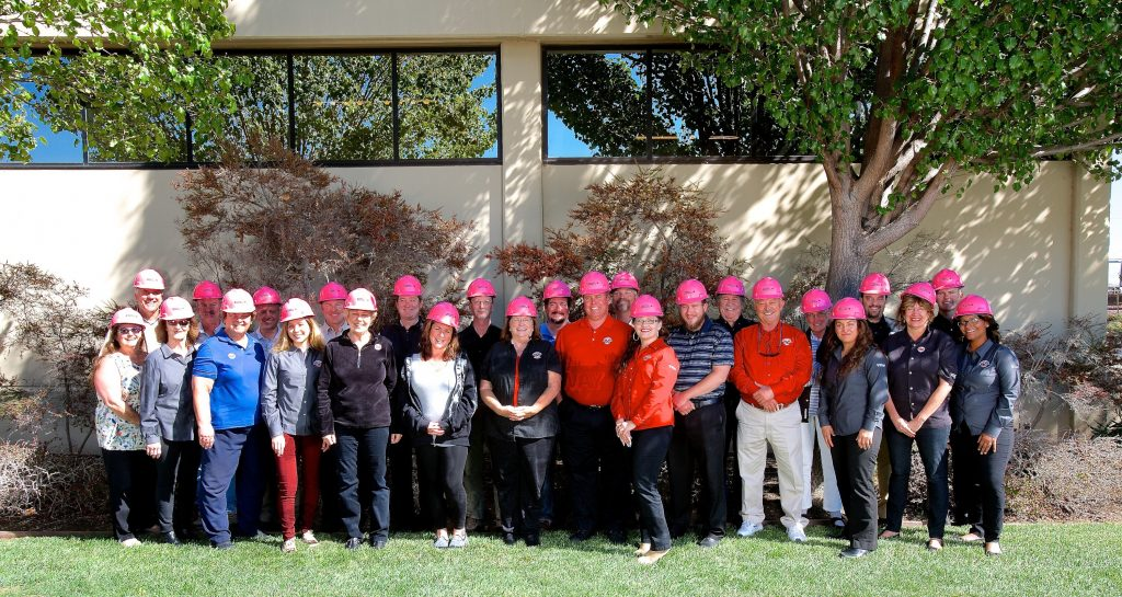 PMI construction workers proudly pose wearing their EMCOR/ PMI Pink Hard Hats.